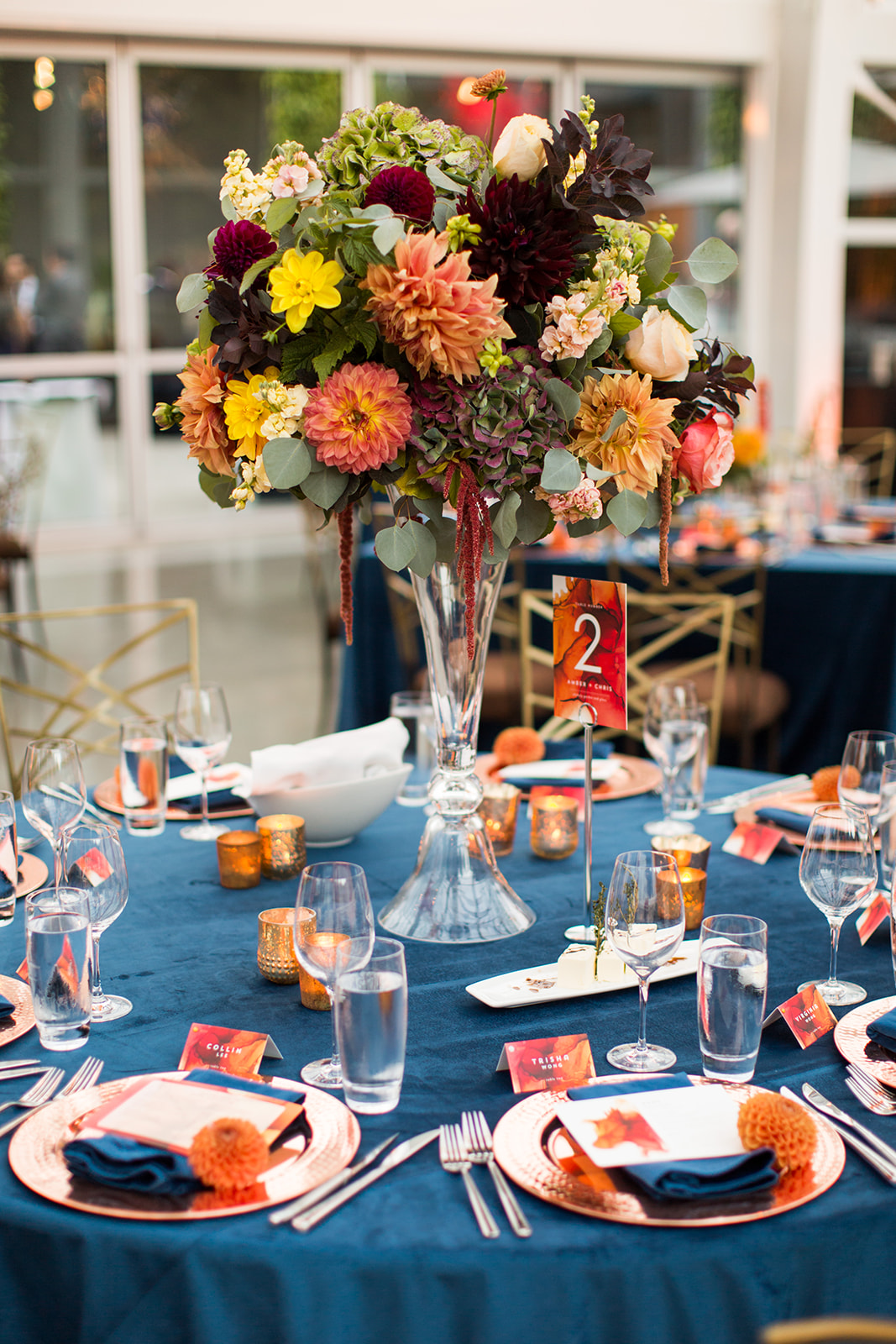 Elevated wedding centerpieces with fall flowers in oranges, Burgundy and yellow colors on navy velvet linens in the Chihuly glasshouse | Flora Nova Design Seattle