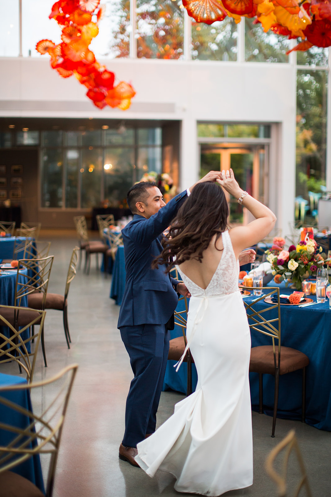 Bride and groom dancing around their reception tables at a fall Chihuly wedding