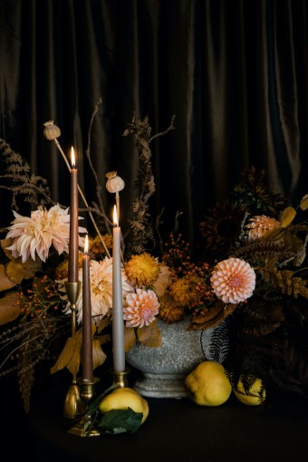 Fall floral centerpiece with peach colored dahlias, brown taper candles, and quince in stone vase, on brown linen - Decorating for the Holidays - Flora Nova Design Seattle