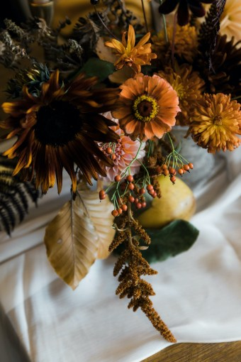Thanksgiving floral centerpiece with chocolate sunflowers, orange zinnias, dried leaves, yellow chrysanthemums, quince fruit