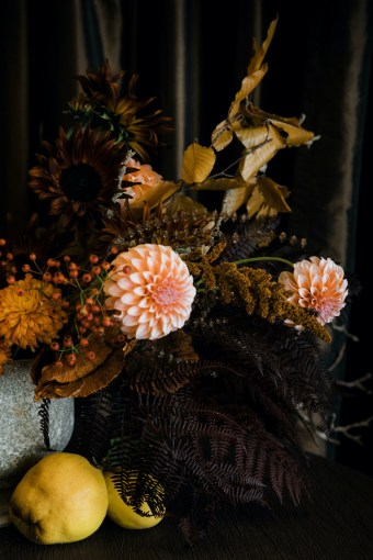 Fall texture in a Thanksgiving table centerpiece with peach dahlias, brown sunflowers, rust brown amaranthus, rosehops, and dried fern and fall foliage, with quince fruit