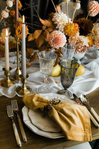 Wooden Thanksgiving table with sheer table runner, yellow velvet napkin, crystal cut glasses, taper candles, and flower centerpiece with orange dahlias