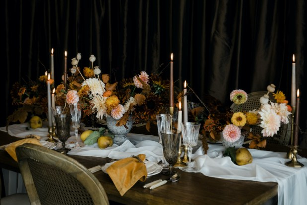 Thanksgiving table with fresh flower centerpieces containing peach colored dahlias, yellow zinnias, and fall textures, on wooden table with ivory sheer table runner, mustard yellow napkins, taper candles, Provence chairs - Decorating for the Holidays - FLORA NOVA DESIGN SEATTLE