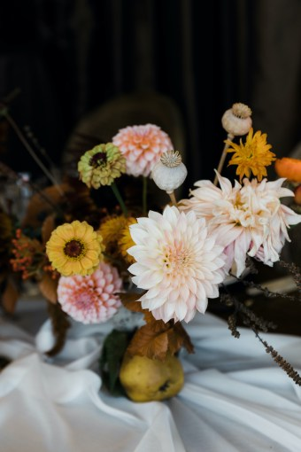 Thanksgiving centerpiece with peach dahlias, yellow zinnias, poppy pods, quince, on ivory sheer linen table runner
