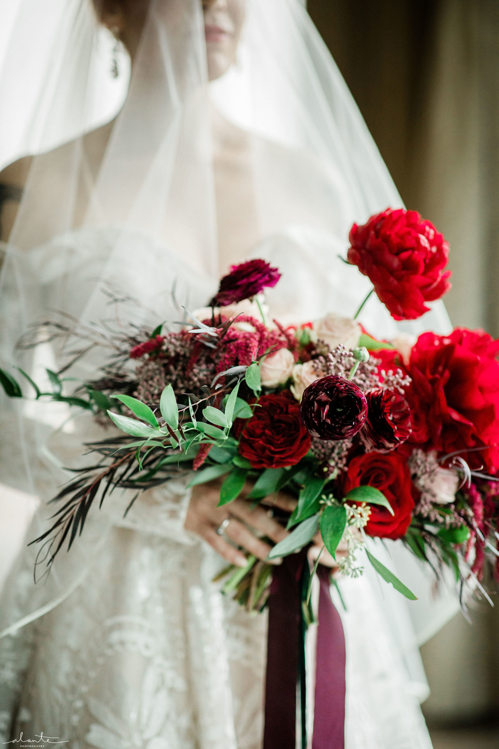 Red peonies and ranunculus along with winter foliages make for a romantic winter bridal bouquet. | Flora Nova Design Seattle