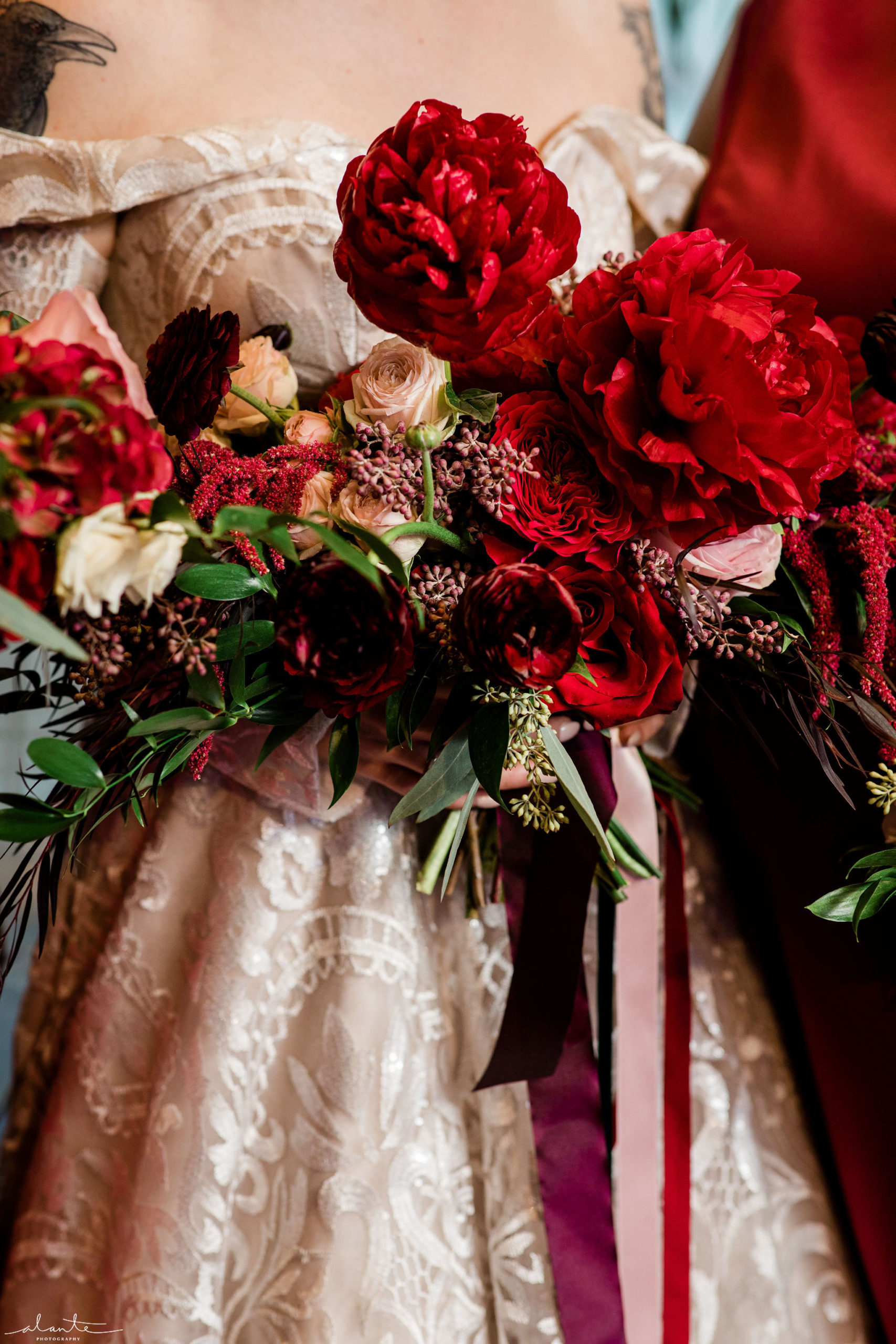 Burgundy and pink ribbon streamers cascade from a red peony bridal bouquet designed by Flora Nova Design