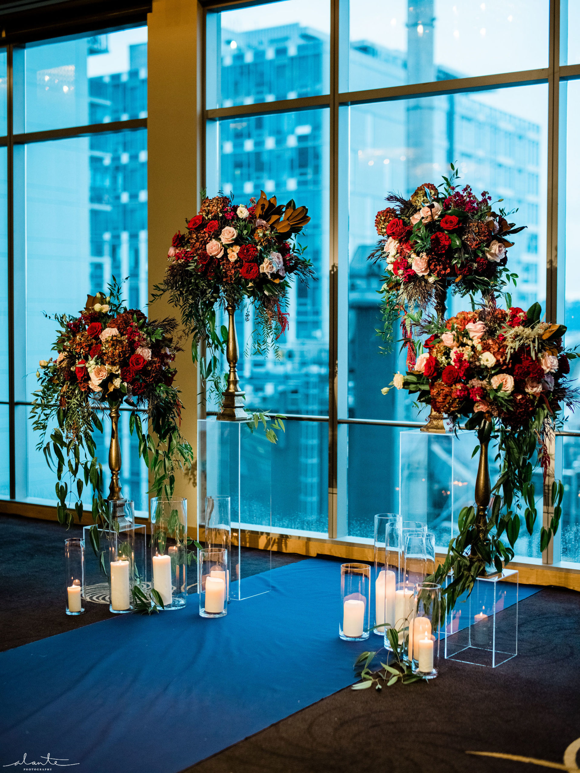 Four tall floral arrangements in red and blush winter flowers along with pillar candles and an unusual navy aisle runner.