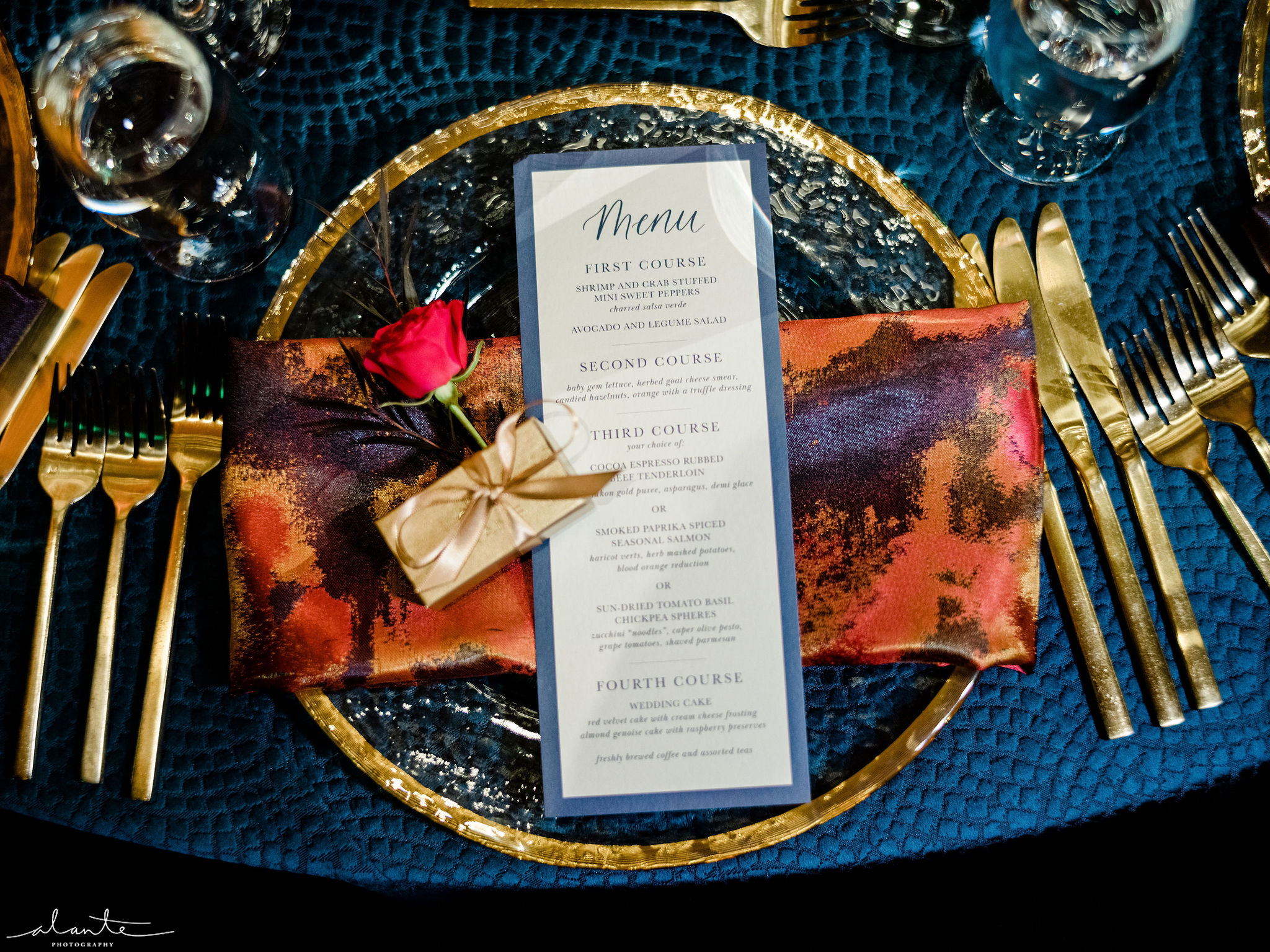 Winter wedding place setting with a red rose on the menu card, navy linens and gold flatware and charger plate.