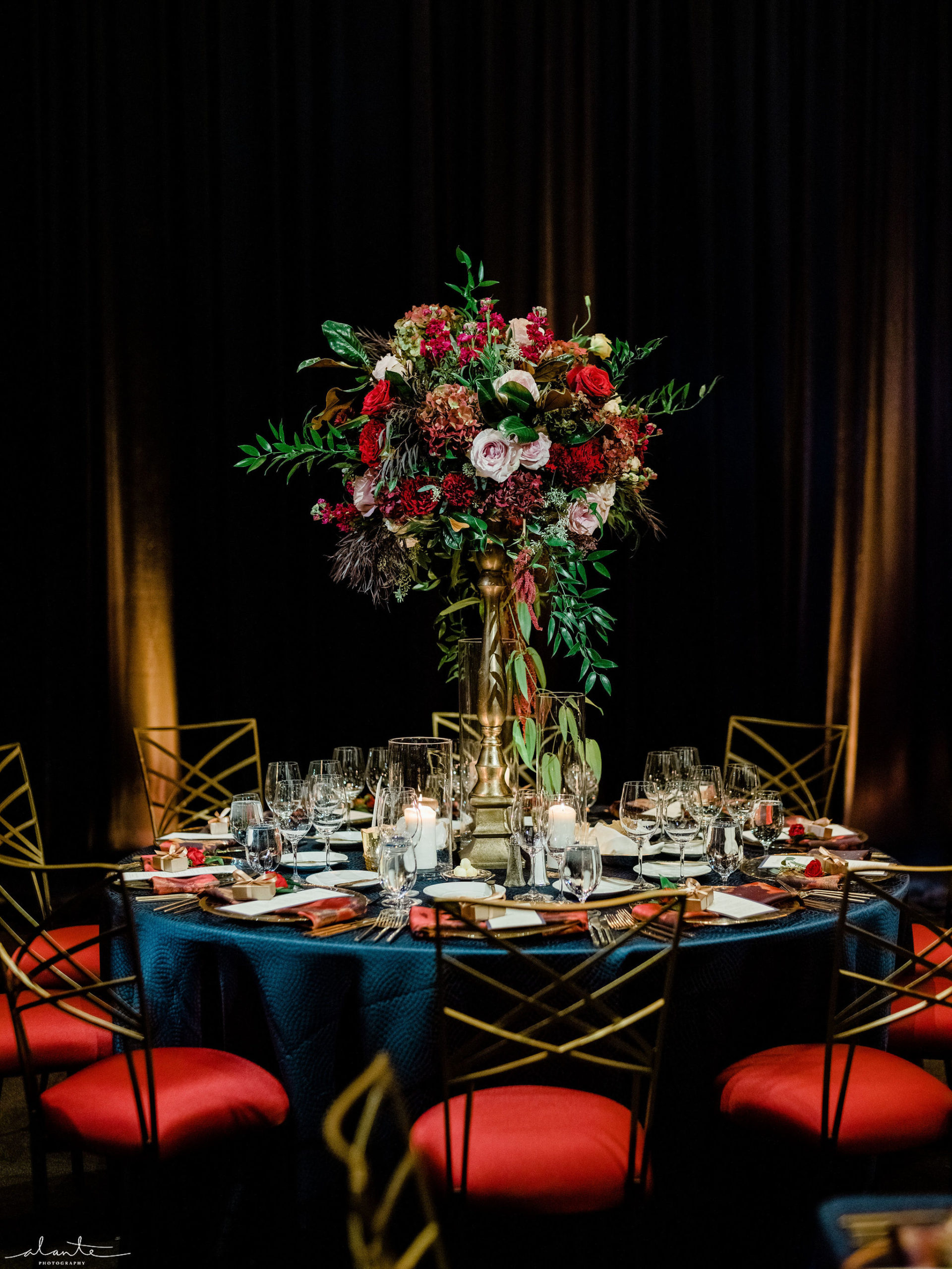 Navy blue linen with a tall floral centerpiece in burgundy and blush for a winter wedding reception designed by Flora Nova Design Seattle