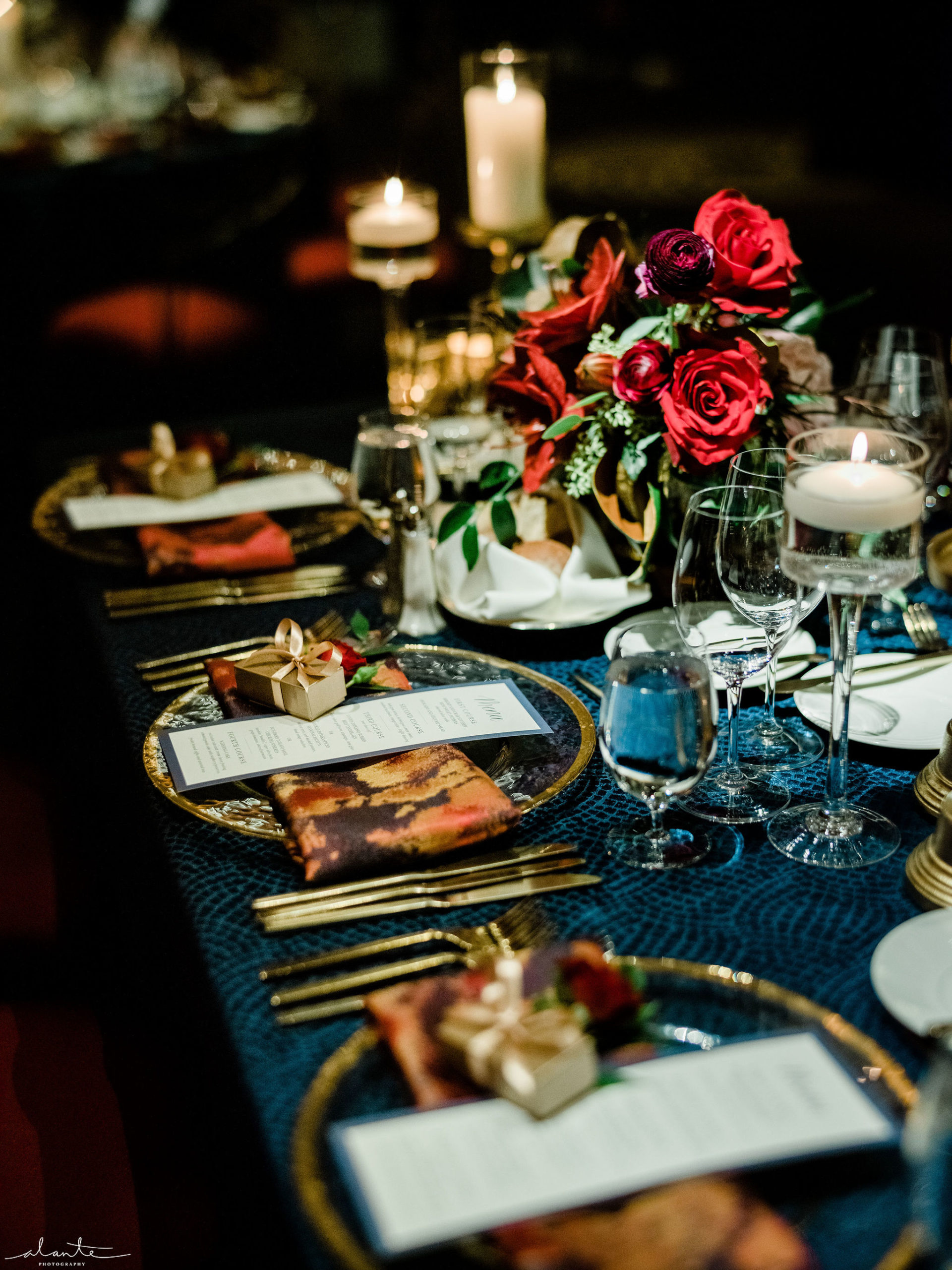 Red rose centerpiece at a December wedding with gold rimmed charger plates and gold flatware.