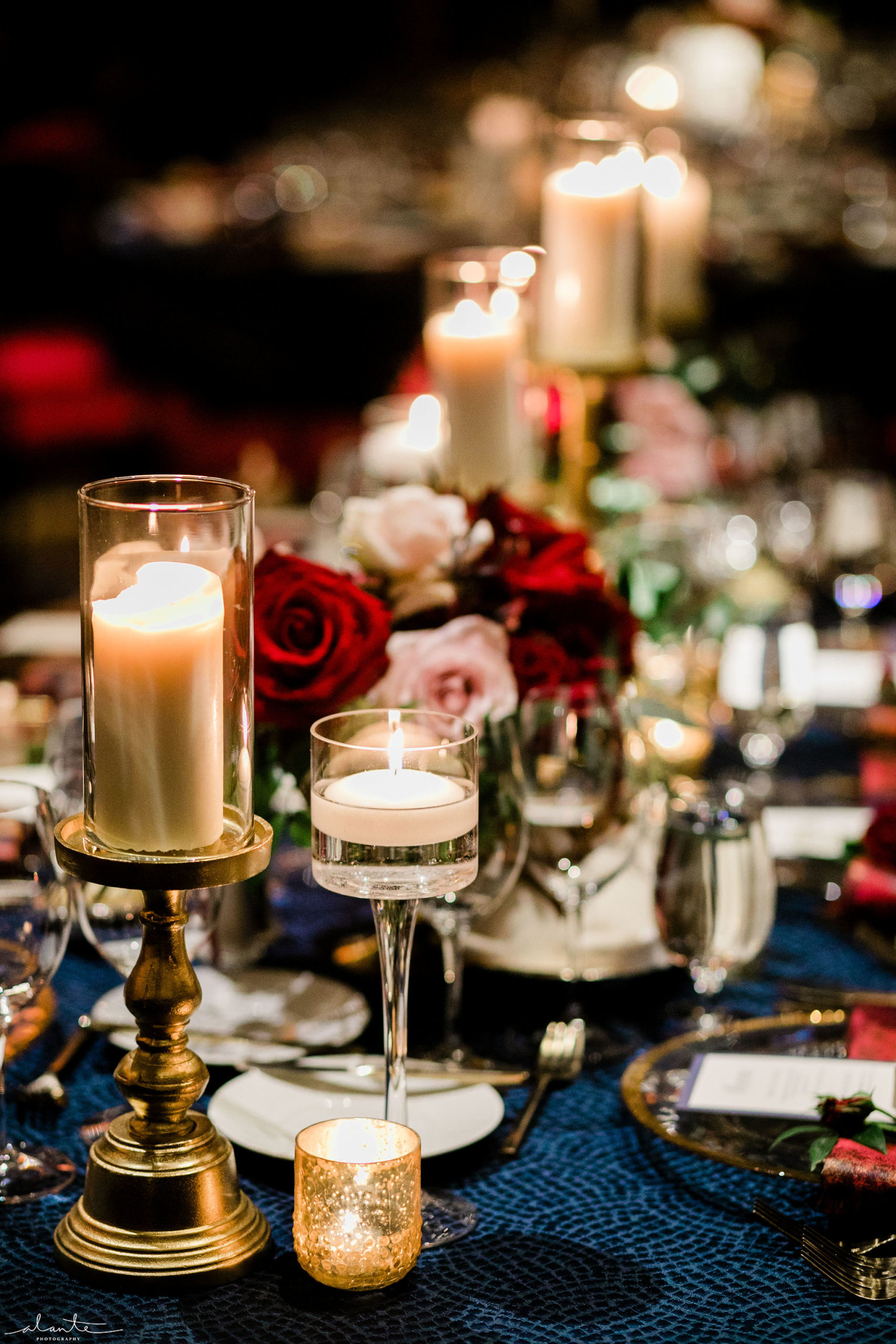 Candlelit tabletop with a red rose centerpiece on navy blue linens for a winter wedding reception by Flora Nova Design Seattle