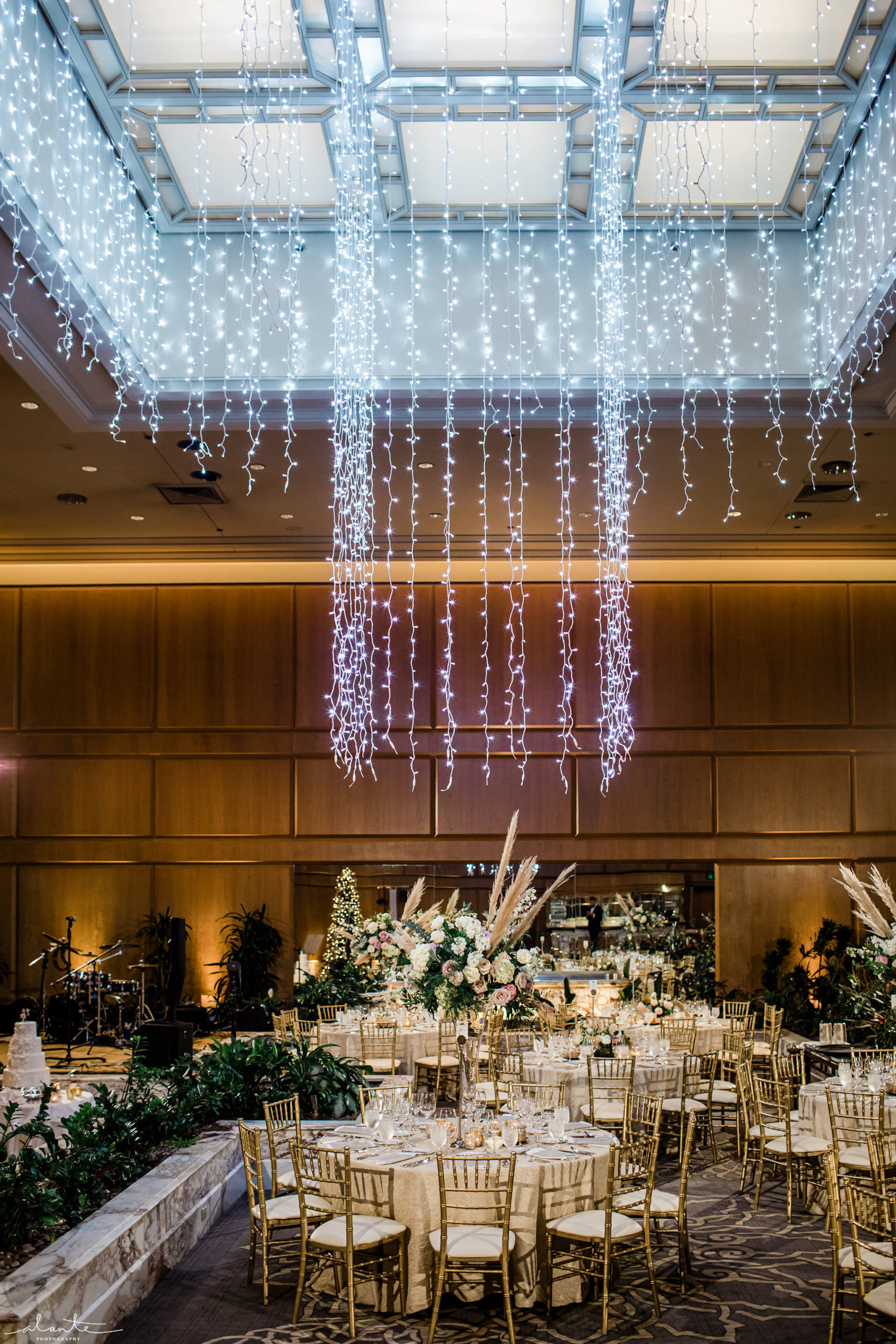 New Years Eve wedding reception with gold tables and chairs and tall white and blush floral with pampas grass under a hanging Christmas light chandelier.