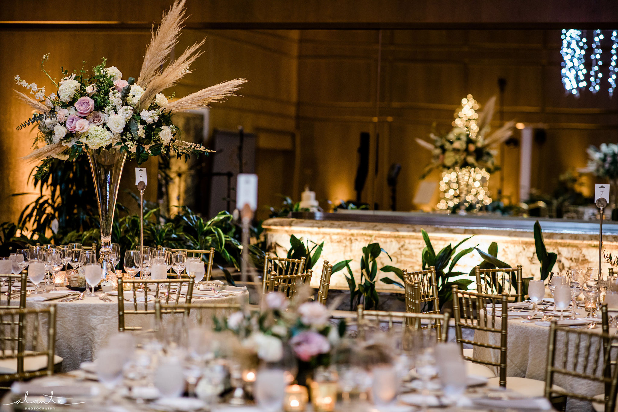 Ballroom winter wedding reception with tall floral arrangements in white and blush flowers with pampas grass on a crystal vase.
