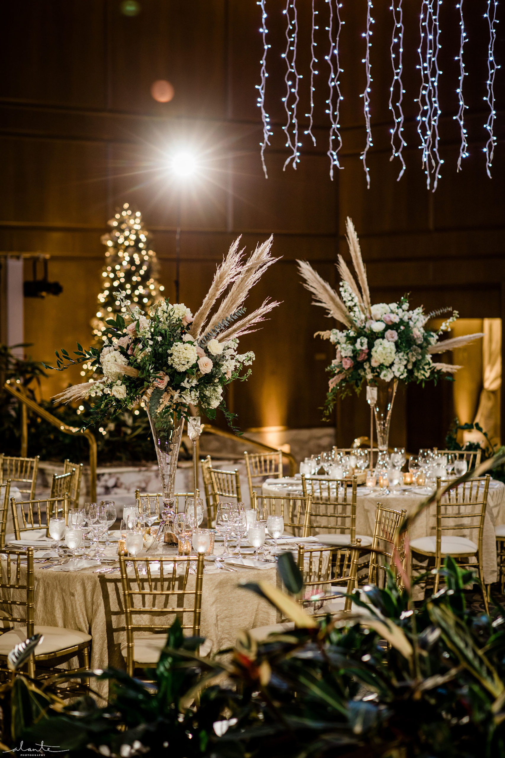 Pampas grass wedding tall white floral centerpieces with gold Chiavari Chairs at a winter reception.