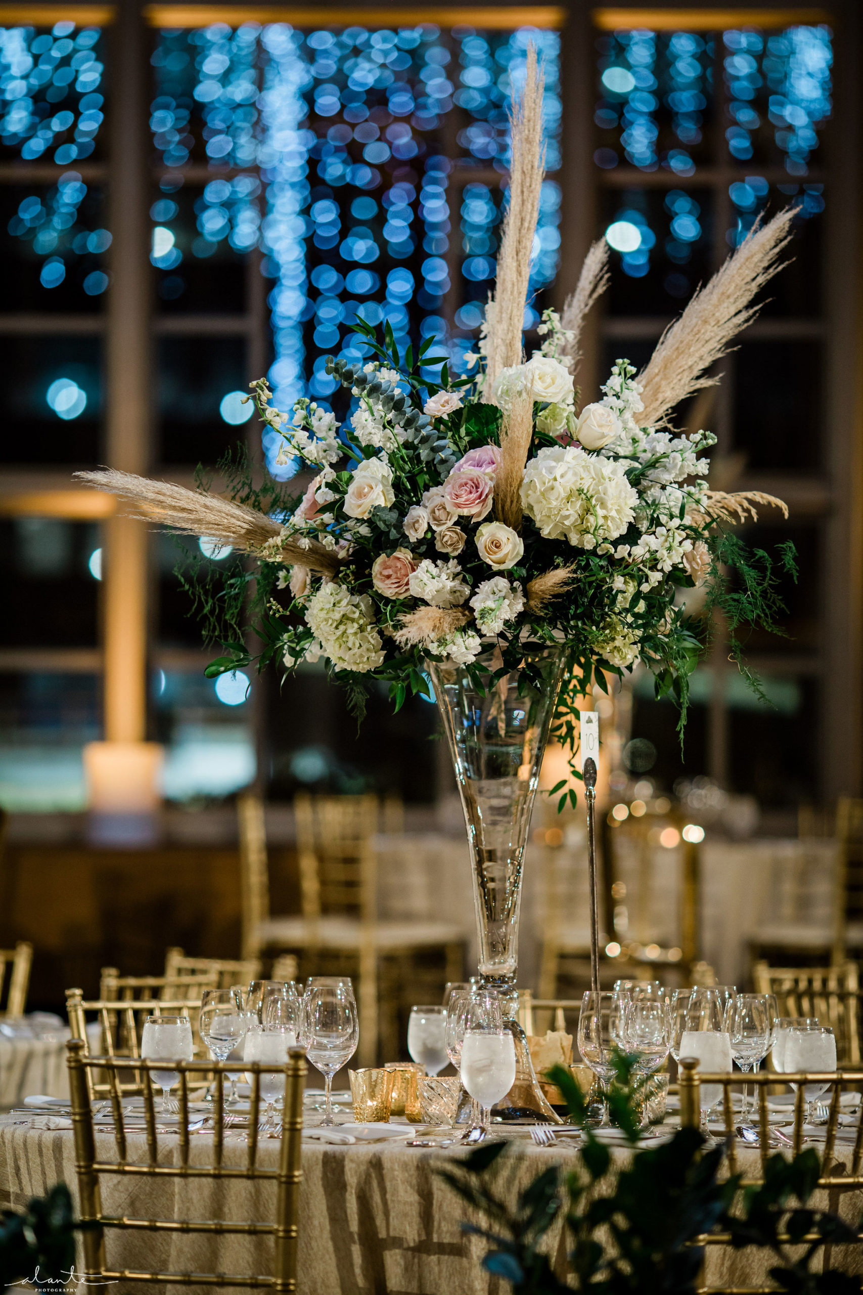 Elevated white and blush floral centerpiece of hydrangea, roses, stock, and eucalyptus with pampas grass on a tall crystal vase.