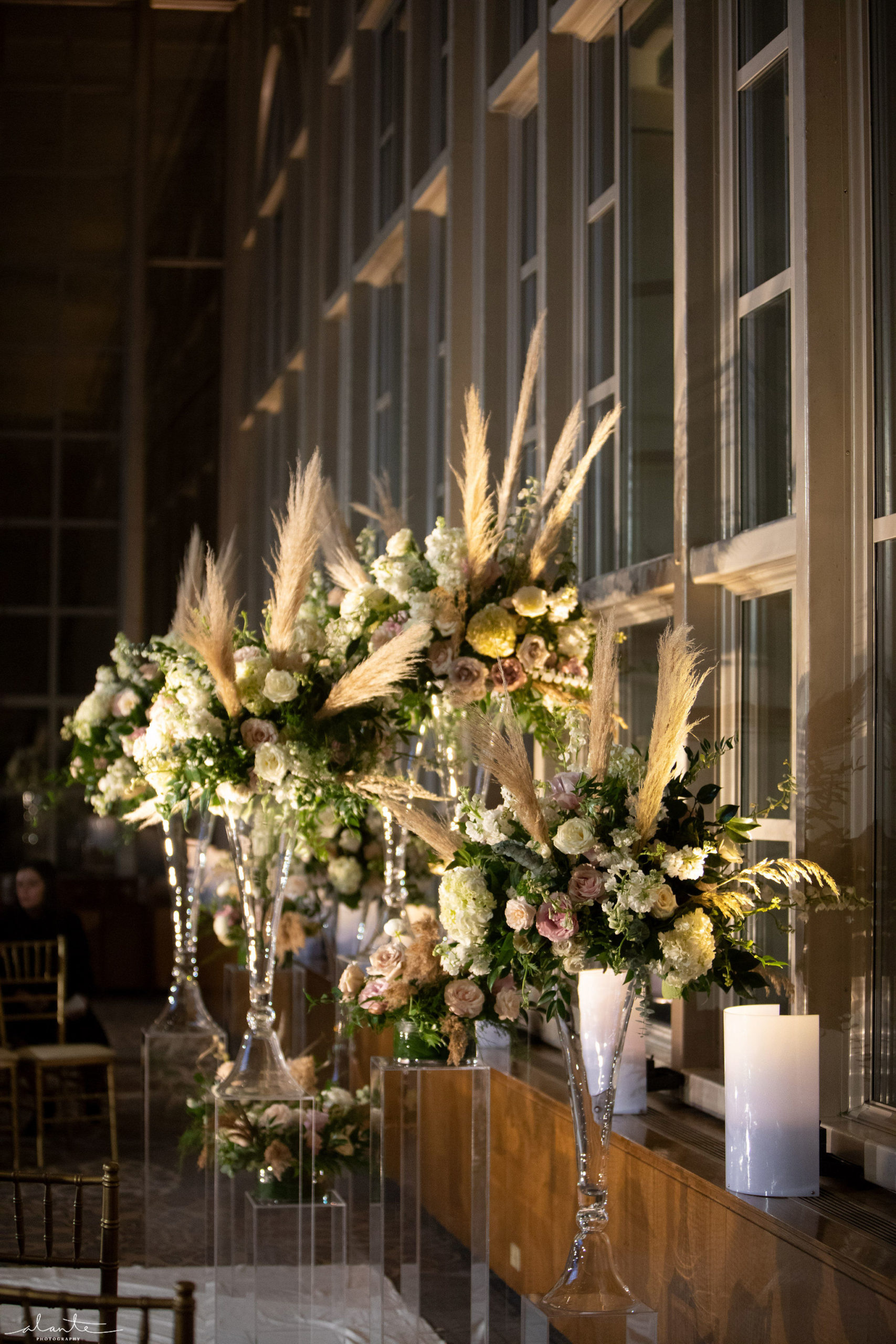 New Years Eve wedding ceremony alter floral arrangements featuring pampas grasses and white and blush flowers.