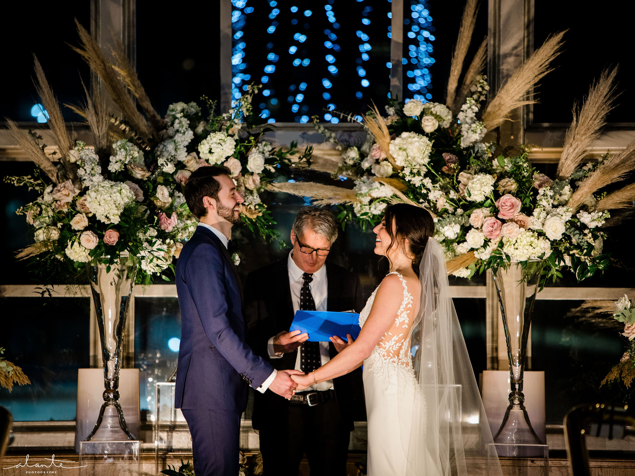 Pampas grass wedding ceremony, tall floral arrangements in white and blush frame the couple.