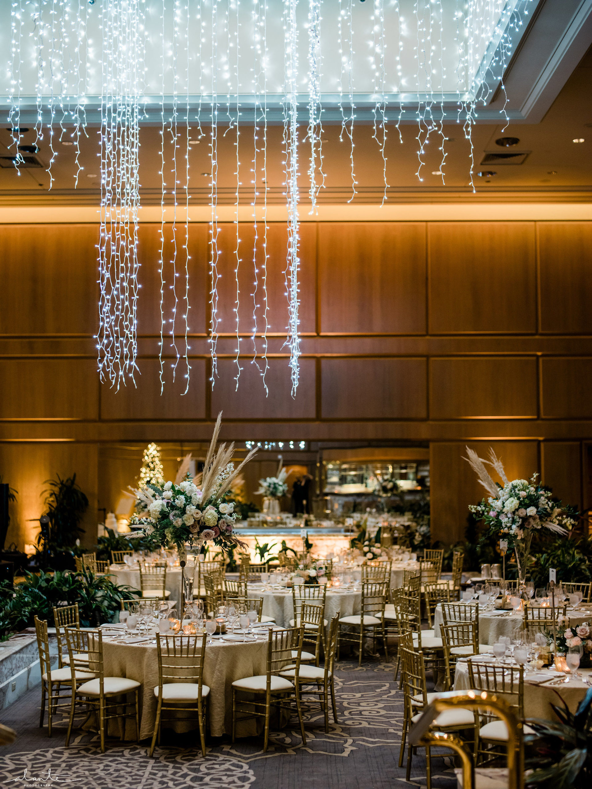 New Years Eve wedding reception, round tables with gold charivari chairs and tall pampas grass centerpieces under a holiday light chandelier.