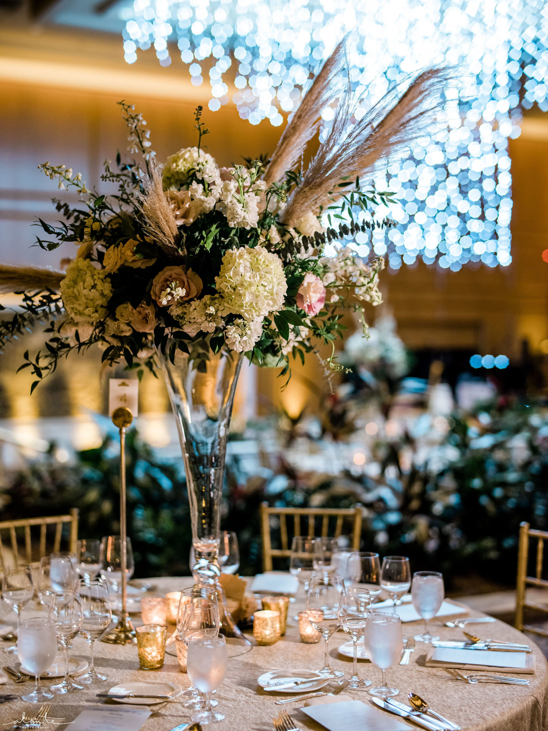 Tall pampas grass wedding centerpiece with white and blush floral on a crystal vase for a winter reception.