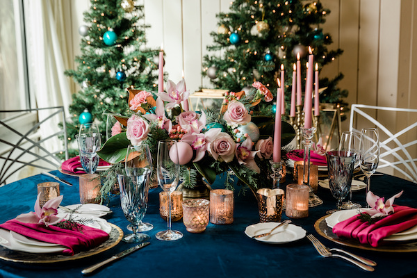 Centerpiece for the holidays with pink roses, pink, orchids, pink ornaments, candles, navy linen, in front of Christmas trees