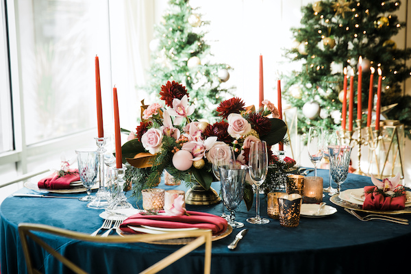 Festive centerpiece for the holidays in red and blush pink on navy linen