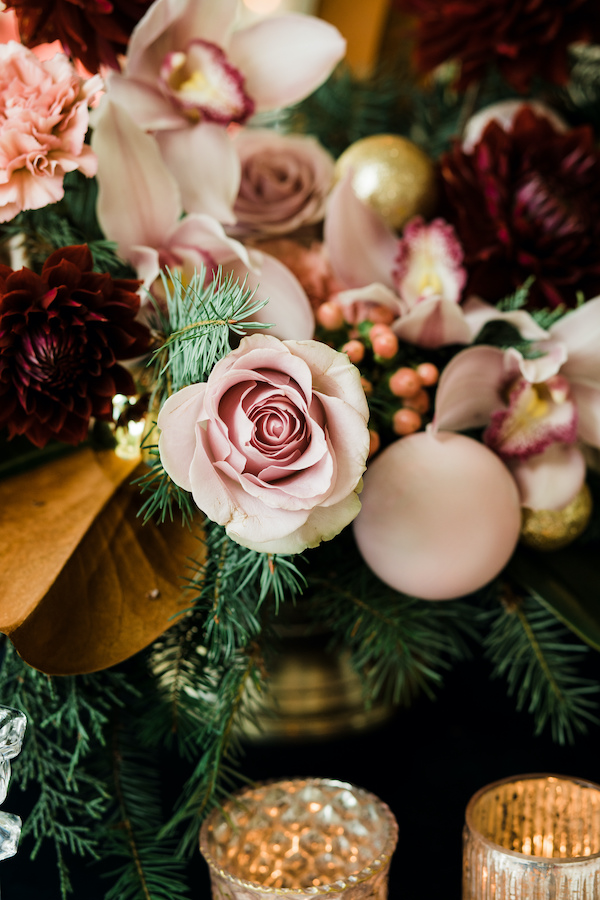 Centerpiece of blush roses, pink ornaments, evergreen, in gold compote