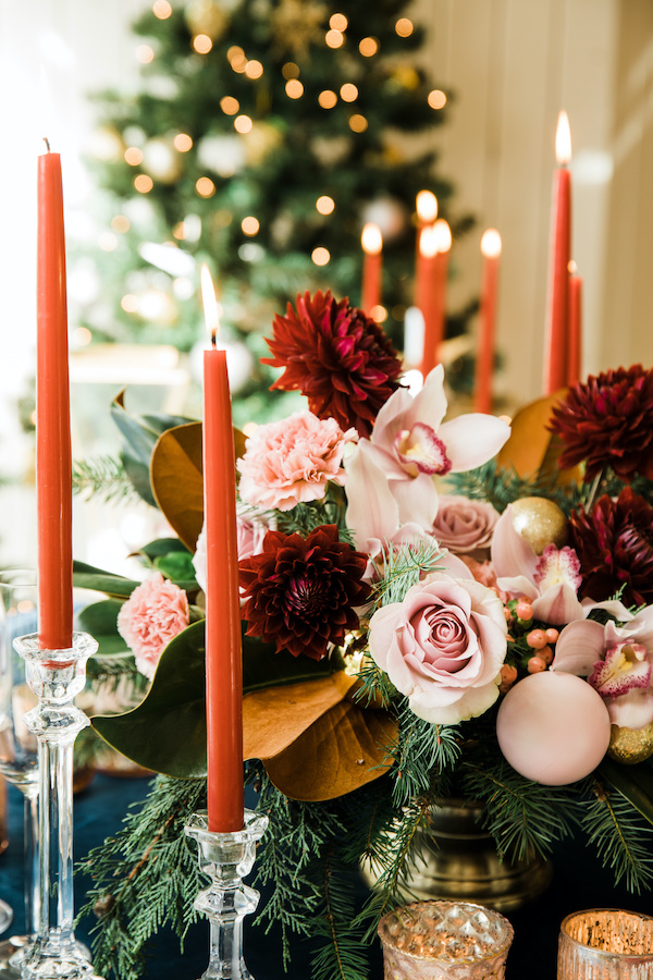 Holiday centerpiece with blush roses, pink orchids, burgundy dahlias, red taper candles, in front of Christmas tree