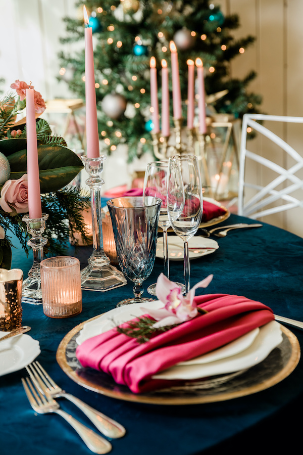 Holiday dinner table with red velvet napkin, pink orchid napkin flower, pink candles, navy linen, and Christmas tree