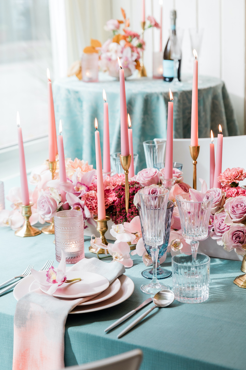 Romantic dinner date table set for two with pink and mauve floral mixed with teal accents.