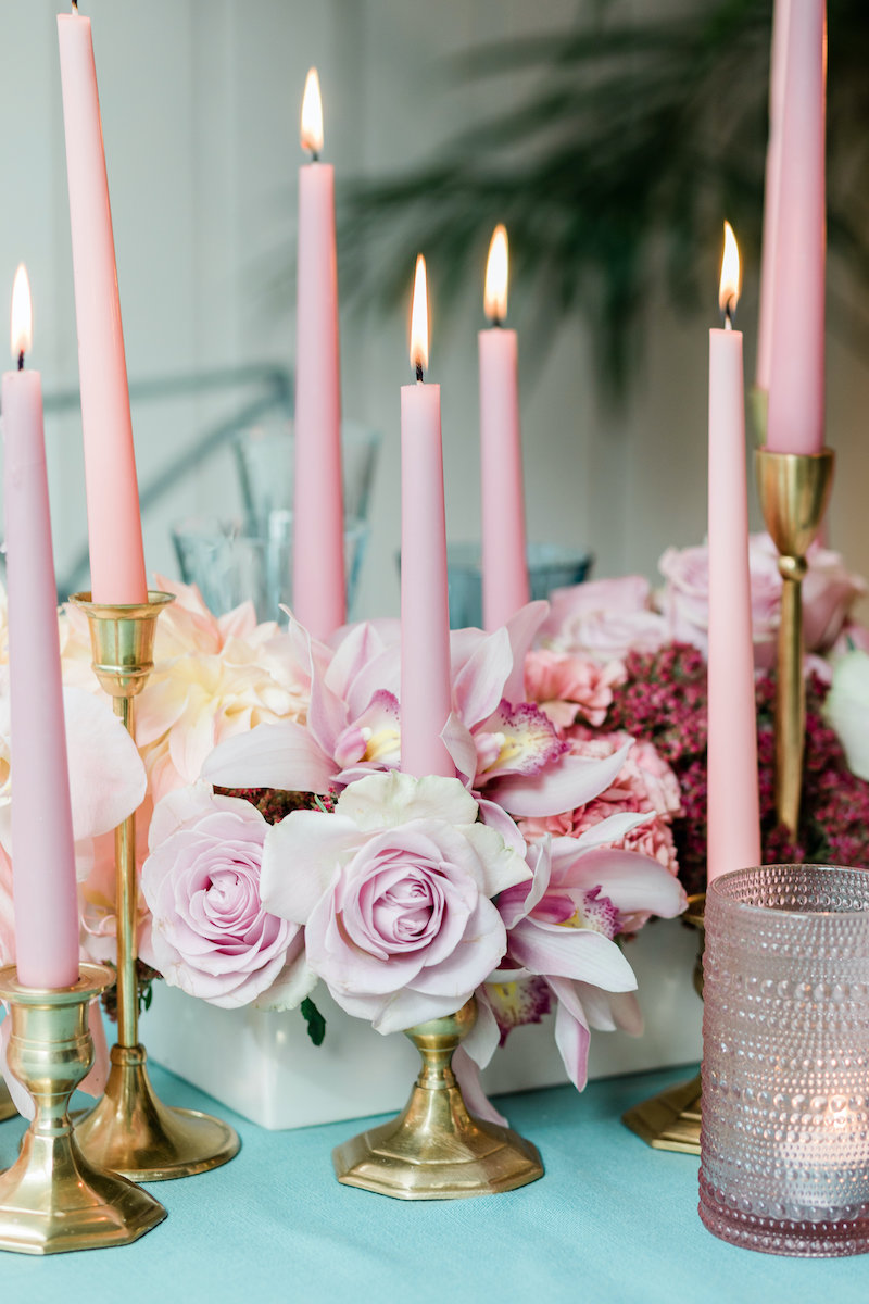 Low pink floral centerpiece of roses and orchids paired with pink taper candles in brass holder on a teal linen.