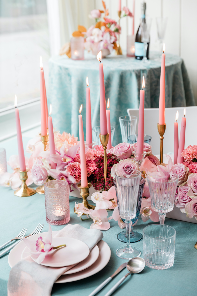 Table set for a modern yet romantic take on an intimate at home date night with pink floral and teal linen.