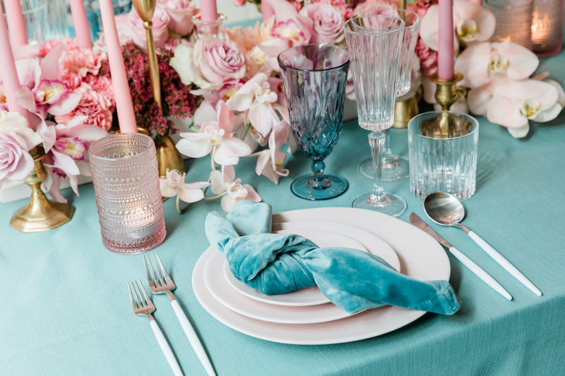 Turquoise velvet napkins and linens are paired with soft pink floral for a romantic dinner place setting of cut glass stemware and pink stoneware plates.