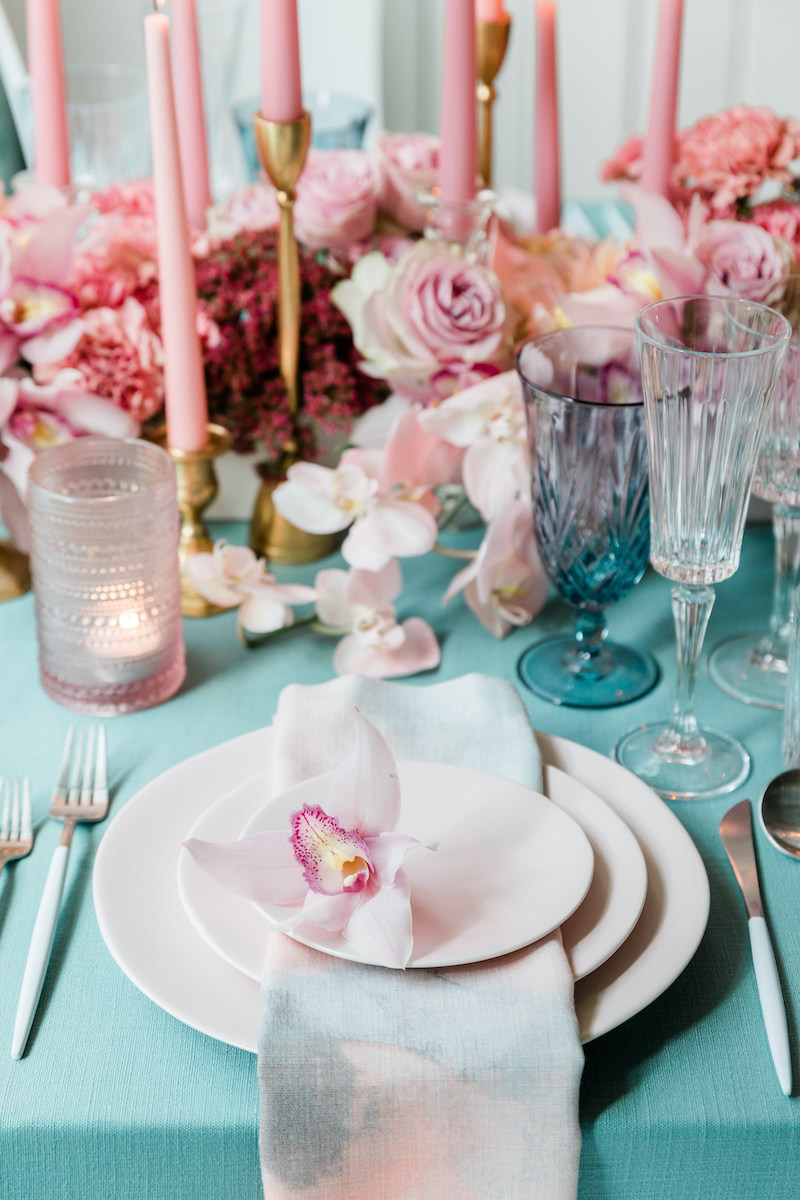 Low monochromatic pink floral centerpiece with pink taper candles are paired with a teal linen for a romantic yet fun dinner party.