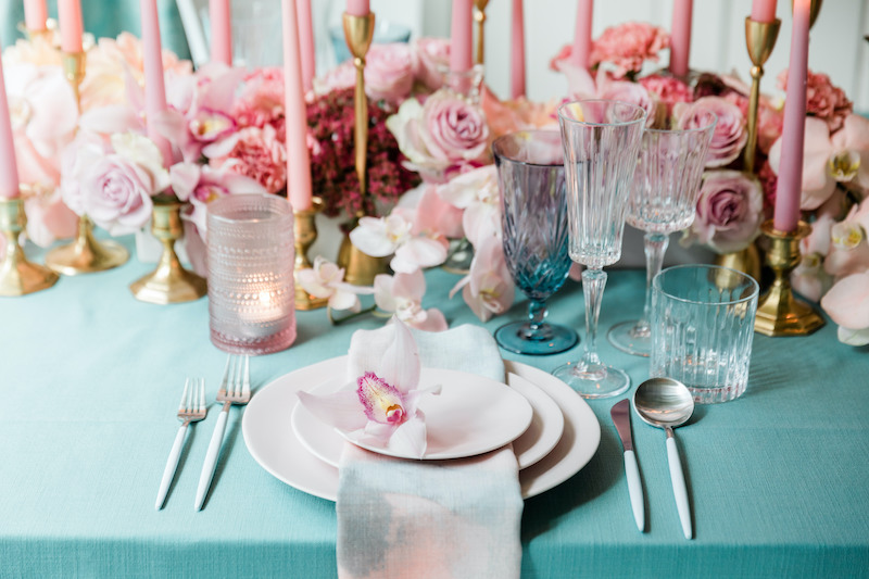 Light pink stoneware plates with a long low pink floral centerpiece with teal accents.