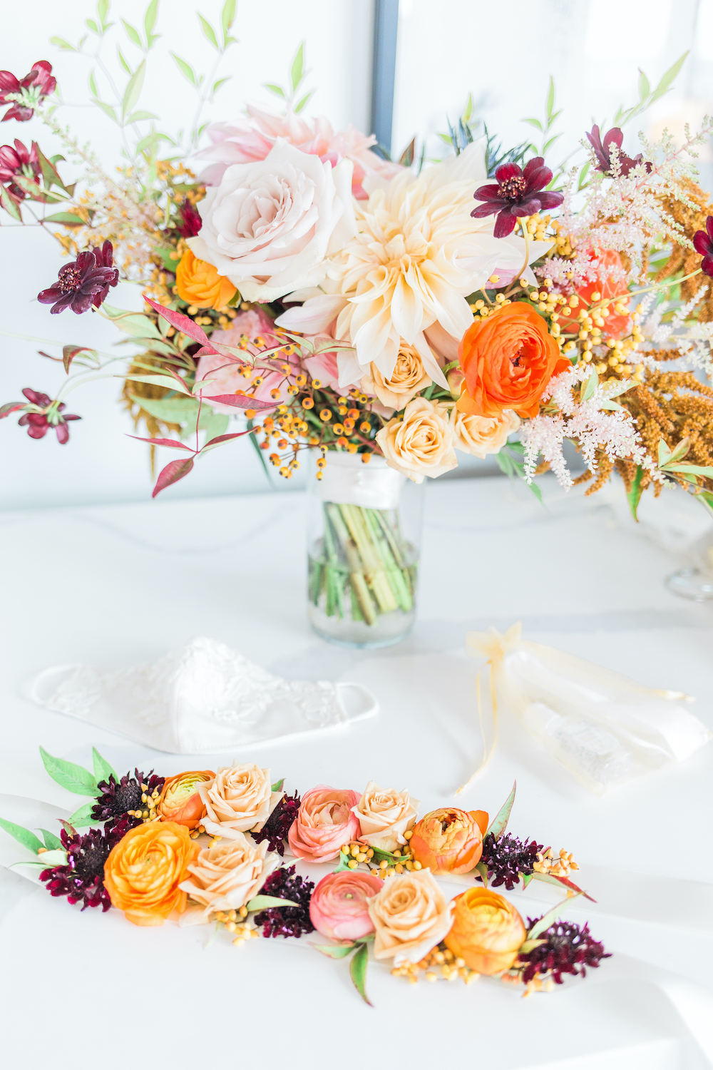 Fall bridal bouquet and floral head bands with dahlias, orange ranunculus, chocolate cosmos, fall foliage
