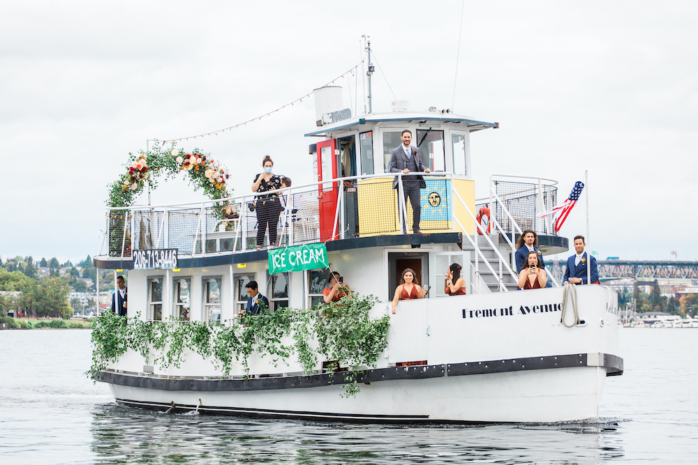 Wedding on small ferry boat in Seattle's Lake Union, decorated in greenery, with bride's maids in maroon dresses, and greenery wedding arch - A Safe Pandemic Seattle Wedding
