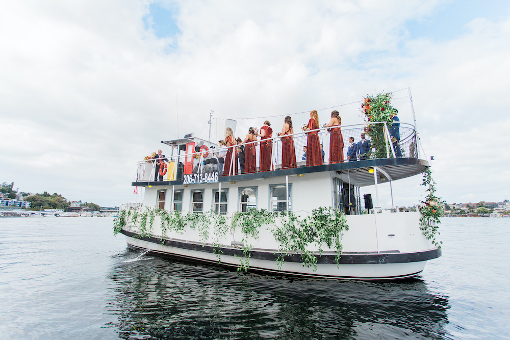 Wedding on a small ferry boat in Seattle's Lake Washington with bride's maids in maroon dresses and greenery decoration
