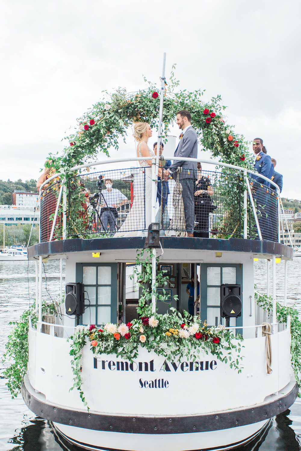 Bride and groom holding hand at fall wedding on Seattle's Lake Union with greenery arch and socially distanced guests - a safe pandemic wedding in Seattle