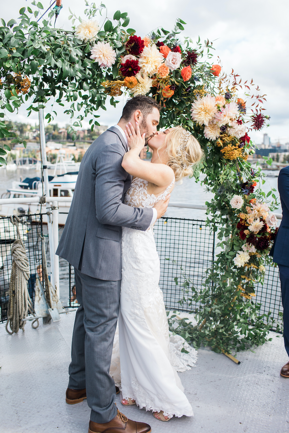 Bride and groom kissing under greenery and fall floral arch