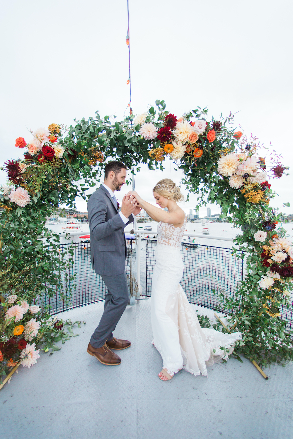 Bride and groom dancing under their wedding arch on a boat in Lake Union Seattle - A Safe Pandemic Wedding