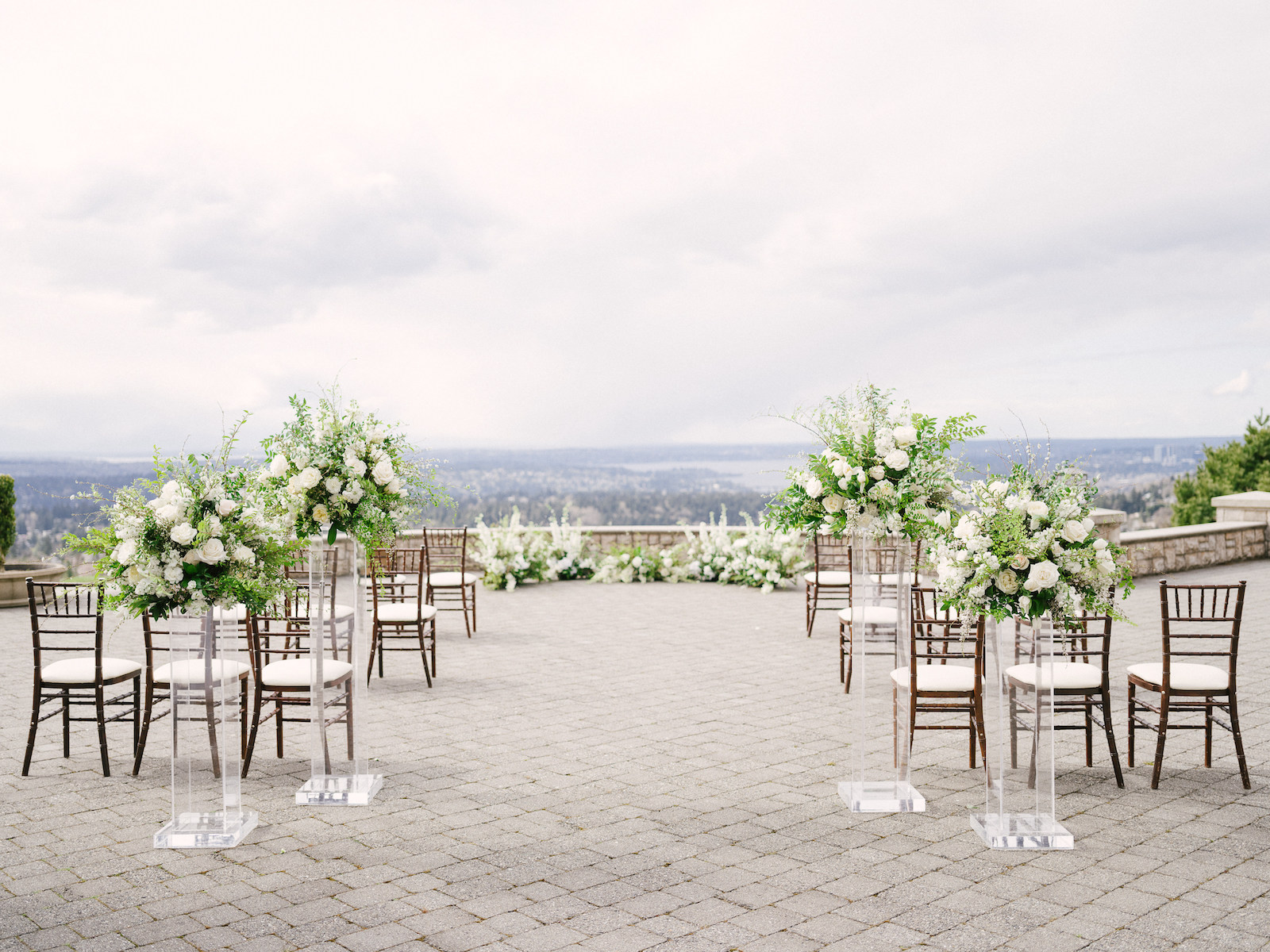 Spring wedding setup at Prestwick Patio at Newcastle Golf Club, with grounded floral arch, and tall white and green floral arrangements at the aisle entrance on top of clear lucite pedestals, with brown Chivari chairs