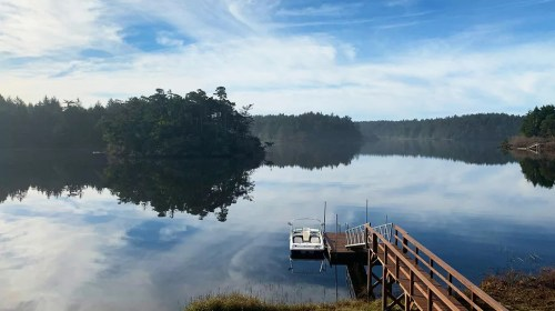 Boat at private dock of Floras Lake Vacation Rental