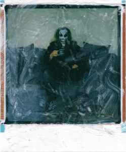 polaroid photo of man with joker face sitting on couch