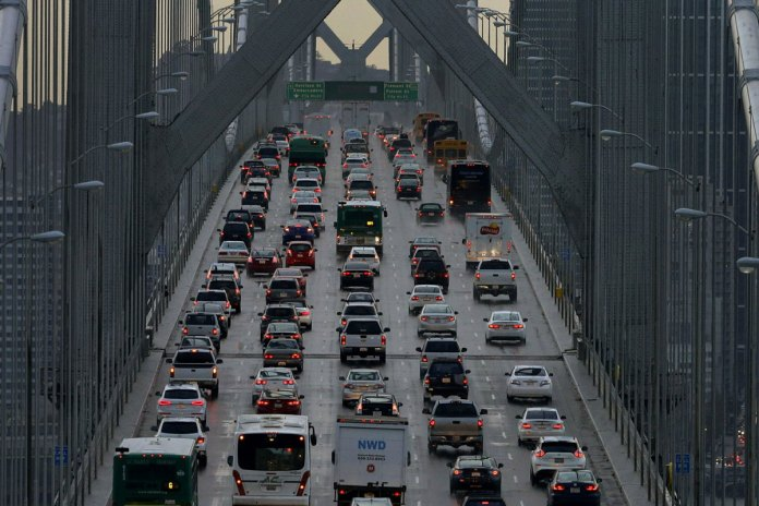 FILE - In this Dec. 10, 2015 file photo, vehicles make their way westbound on Interstate 80 across the San Francisco-Oakland Bay Bridge as seen from Treasure Island in San Francisco. As the Trump administration rolls back environmental and safety rules for the U.S. energy sector, government projections show billions of dollars in savings reaped by companies will come at a steep cost: increased premature deaths and illnesses from air pollution, a jump in climate-warming emissions and more derailments of trains carrying explosive fuels. (AP Photo/Ben Margot, File)