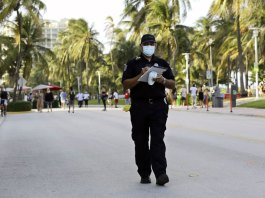 Miami Beach code compliance officer, walks along Ocean Drive