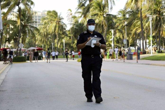 Miami Beach code compliance officer, walks along Ocean Drive