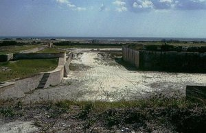 """The landward side of Fort Pickens has a dry ditch, with a counterscarp wall and glacis, which protected the main fort wall from direct cannon fire, and provided another position for infantry to defend the fort from (the """"covered way""""). The ditch was previously much deeper than at present. The original depth can be visualized with the knowledge that the stairs leading to the covered way meet at the orignal level of the bottom of the ditch. The seaward side of Fort Pickens also had a dry ditch, which was filled sometime in the past."""