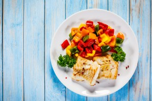 plate with vegetables and fish on it