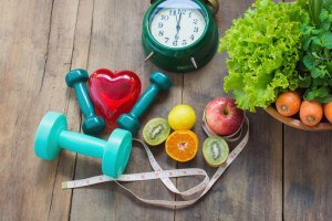 Healthy food concept, fruits and vegetables, apple, kiwi, lemon, carrots and green vegetables dumbbell for weight loss exercises. Red heart and Measuring tape and alarm clock on wooden background