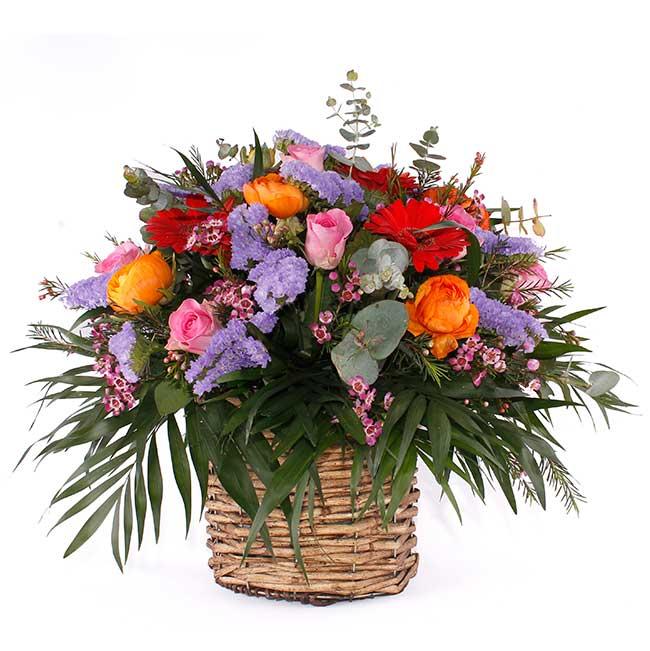 Centro creado sobre una base de mimbre con las mejores rosas, ranúculos, gerberas, flor de cera y statis. Plantas, Cestas y Composiciones. Floristería Pétalos · Tienda Online con envío a domicilio en Alcalá de Henares · Madrid